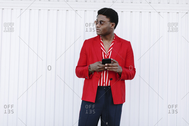 Portrait of a stylish black man wearing red blazer and using cell phone