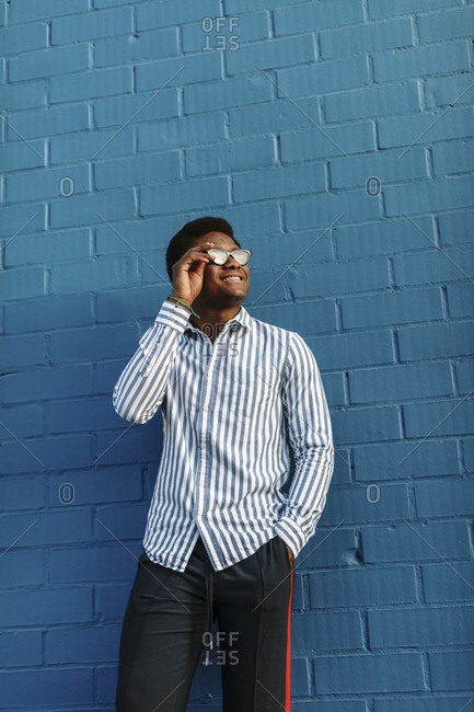 Low angle portrait of a stylish black man wearing blue striped collared shirt
