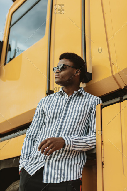 Portrait of a stylish black man wearing blue striped collared shirt leaning on a large yellow vehicle