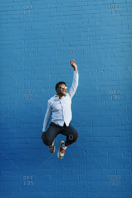 Stylish black man wearing blue striped collared shirt jumping in the air