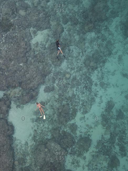 Couple swimming in ocean, Sumbawa, Indonesia