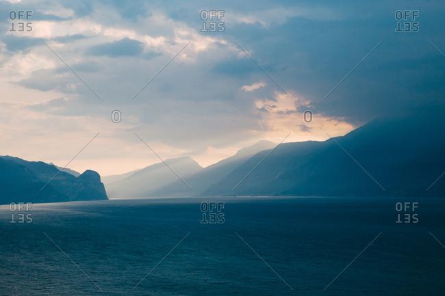 Sunrise light rays shine over mountains onto Lake Garda in Italy