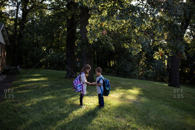 Brother and sister siblings waiting for school bus sunny morning
