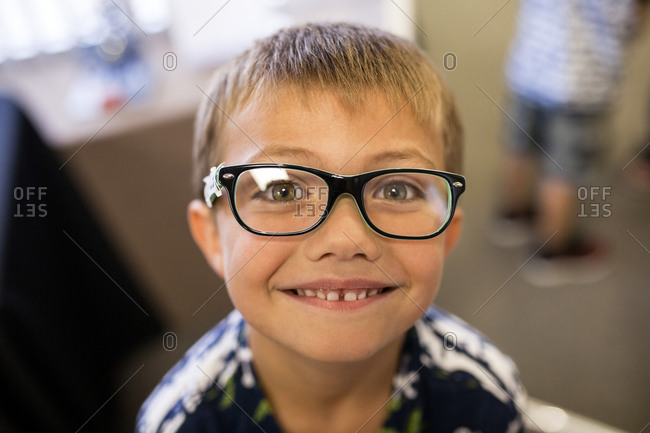 Elementary age boy excited to be wearing glasses in doctors office