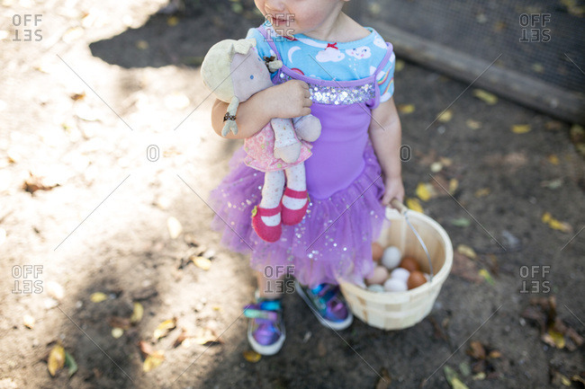 Happy toddler girl with baby doll dressed up with basket of eggs