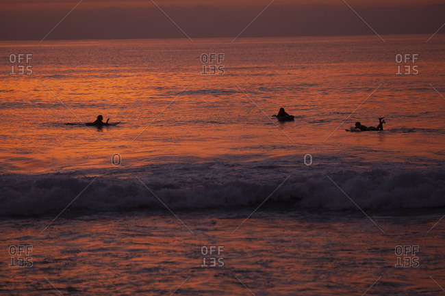 Surfers in water at sunset