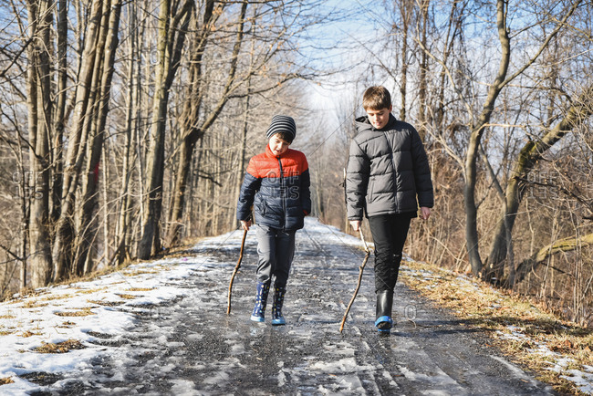 Two boys dragging sticks on the ground on snowy trail in winter.