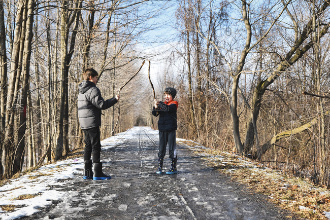 Two boys play fighting with sticks on a snowy trail in winter.
