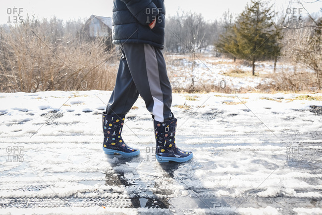 Cropped shot of child in rubber boots walking on a slushy winter trail