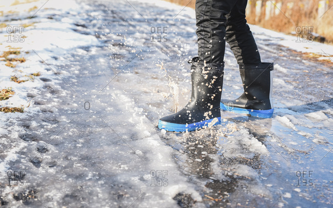 Cropped close up of rubber boots splashing in a slushy puddle.