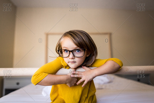 Young girl with glasses and yellow dress sitting on bed