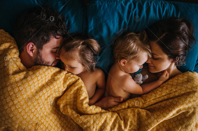 Family of four sleeping together in bed holding children