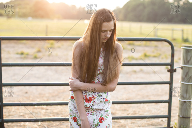 Girl Standing in Front of a Horse Farm Fence at Sunset, Looking Down