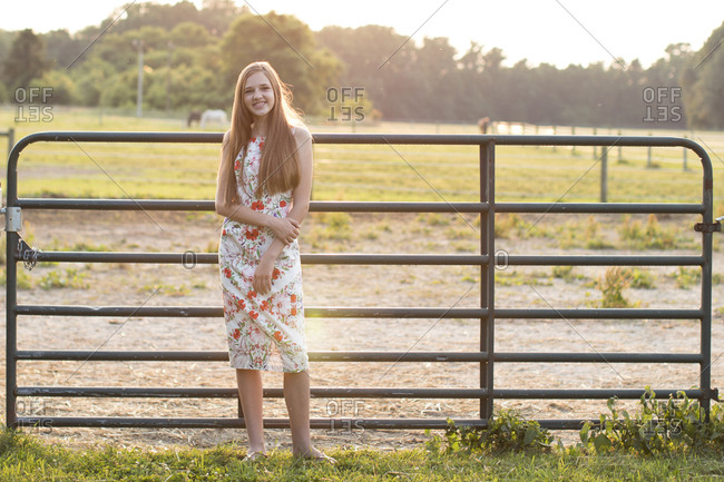 Smiling Teenage Girl Standing in Front of a Horse Farm Fence at Sunset