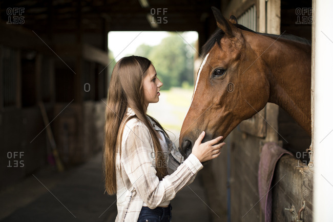 Teenage Girl Makes Eye Contact With Brown Horse in Stall in Barn