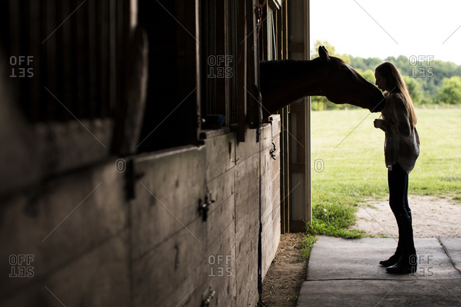Silhouette of Teenage Girl Kissing Horse in Stall in Old Barn