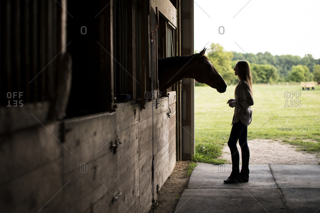 Silhouette of Teenage Girl With Brown Horse in Stall in Old Barn