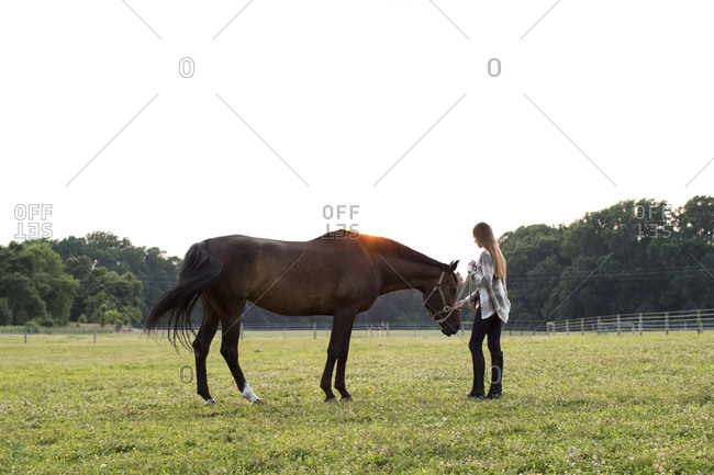 Teenage Girl Stands With Brown Horse in Farm Field at Sunset
