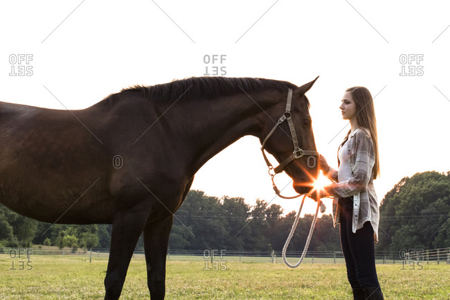 Teenage Girl With Brown Horse in Field at Sunset, With Sun Flare