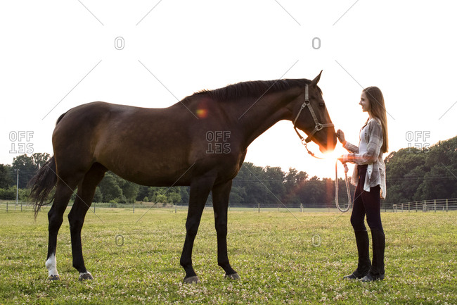 Teenage Girl Smiles at Brown Horse in Field at Sunset, With Sun Flare