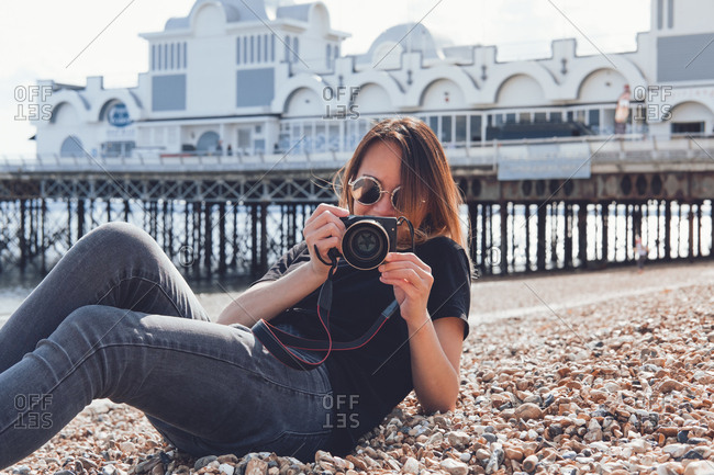 Asian woman taking photos with her camera on the beach