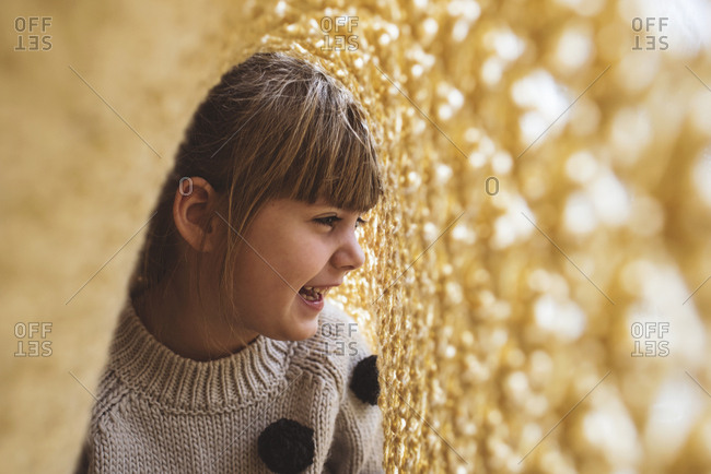 Girl laughing under a yellow blanket