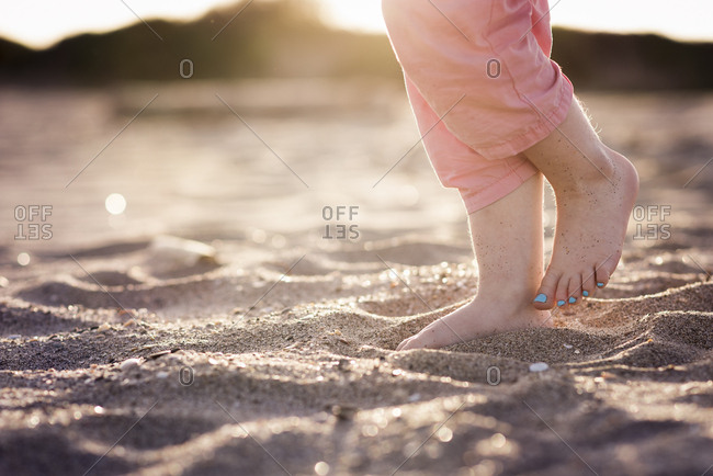 Feet of little girl in sand at beach in evening light with toe nails