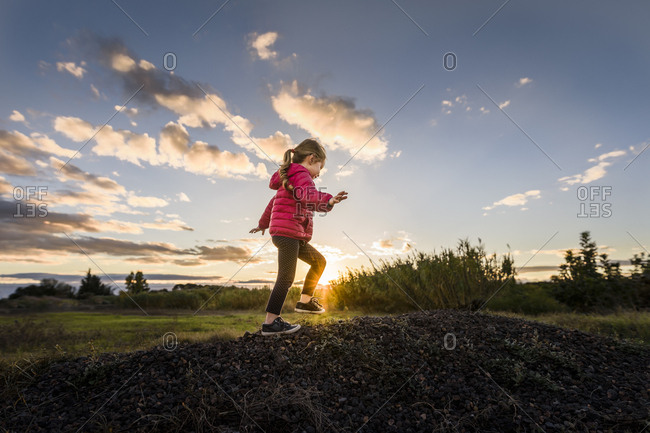 Child climbs pile of stones at sunset with sunburst and cloudy sky
