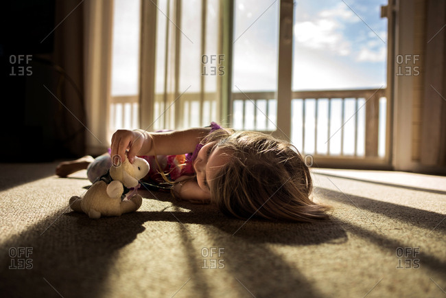 Young girl playing with stuffed animal in beautiful sunlight