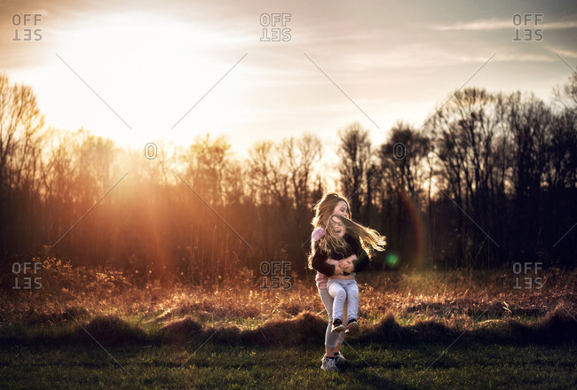 Two young girls twirling and laughing in the sunshine