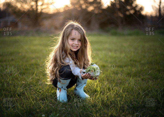 Happy young girl  wearing rain boots and holding green plant