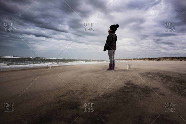 Young girl watching the ocean under cloudy skies