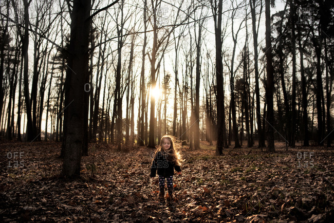 Young girl long curls blowing in the woods during the fall at sunset