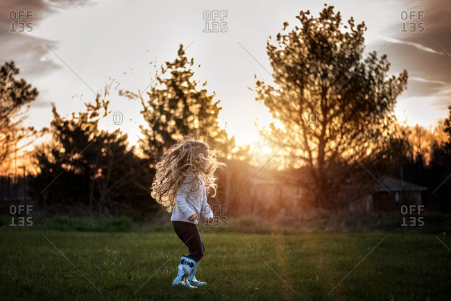 Girl with long curls jumping and playing in rain boots at sunset