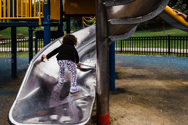 Little girl climbing slide at playground