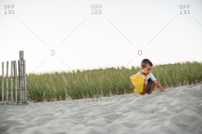 Young boy digging in sand on the beach with a yellow bucket at sunset
