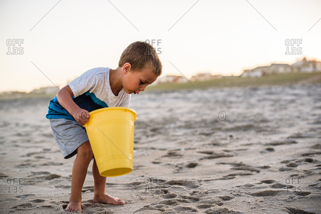Boy on beach holding yellow bucket while searching the sand at sunset