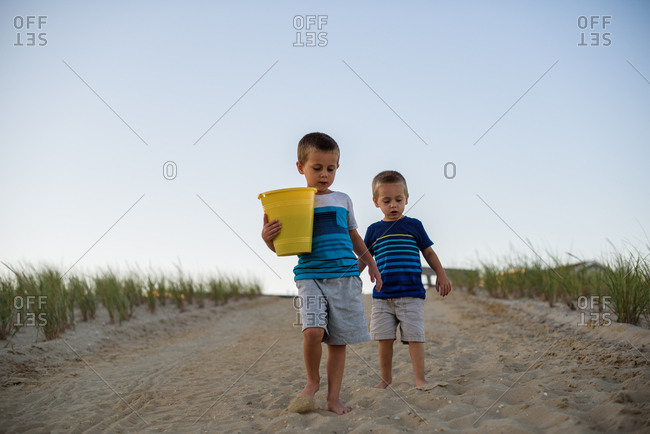 Two boys walking to the beach at sunset while carrying bucket