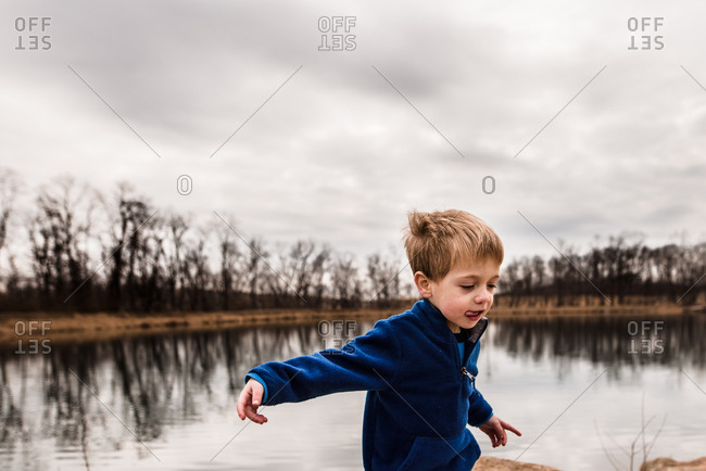 Young boy being silly at the edge of a lake on a cloudy day
