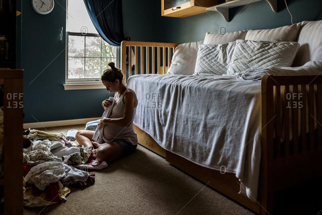 Expectant mother sitting on nursery floor folding baby clothing
