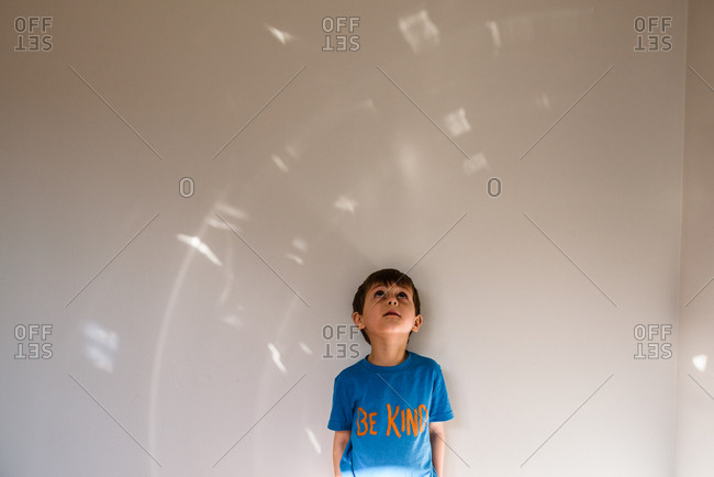 "boy wearing ""be kind"" shirt looking up at light pattern on wall"