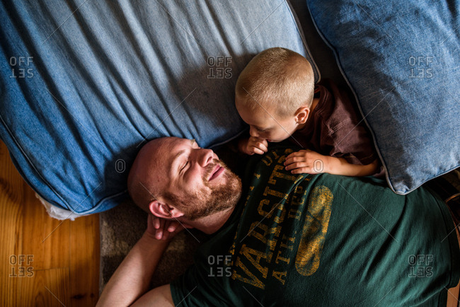 father laying on floor on pillows and smiling at son laying with him