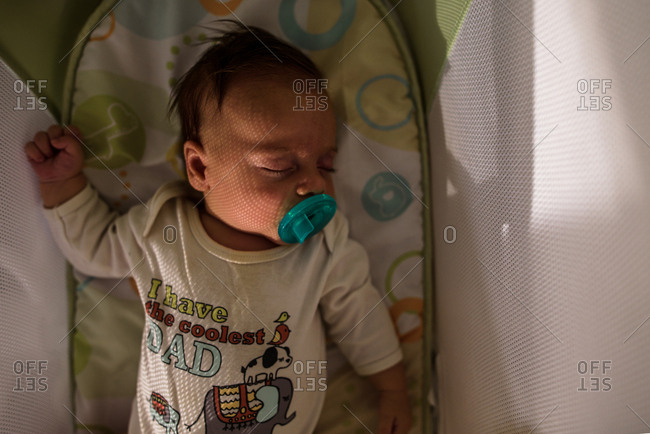 sleeping baby in a bassinet with pacifier and sunlight on face