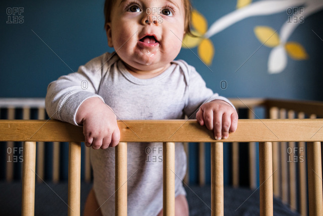 Close up of drooling baby standing and leaning against crib rail