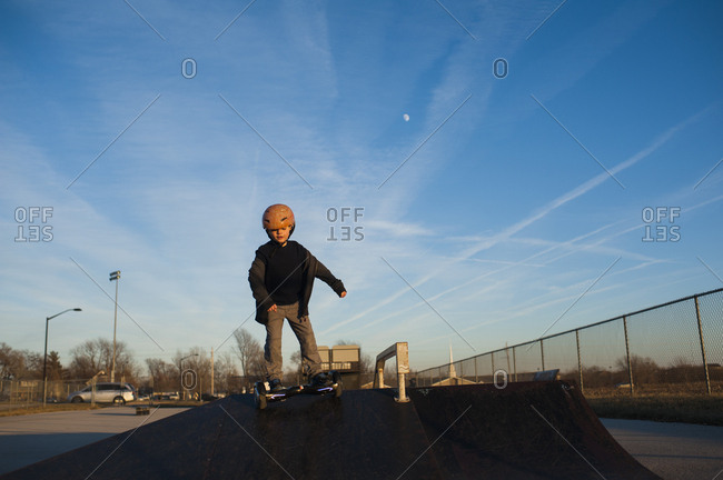 Young boy in helmet riding down pyramid ramp at skate park