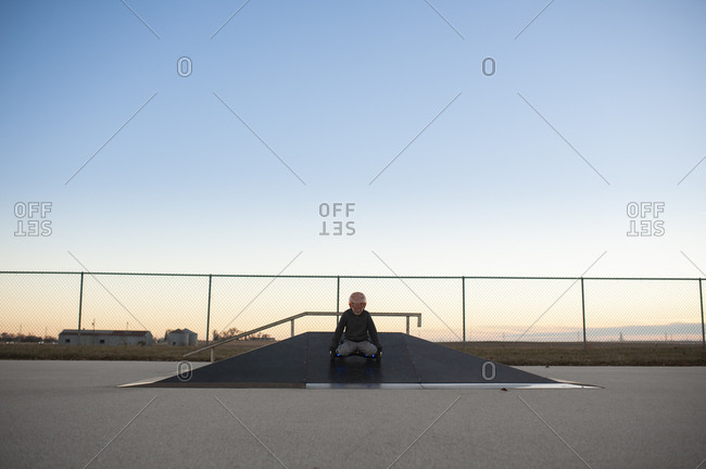 Centered image of boy coming down ramp at skate park on knees