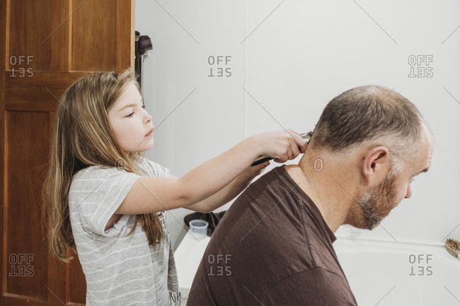 Young girl cutting her fathers hair using electronic clippers