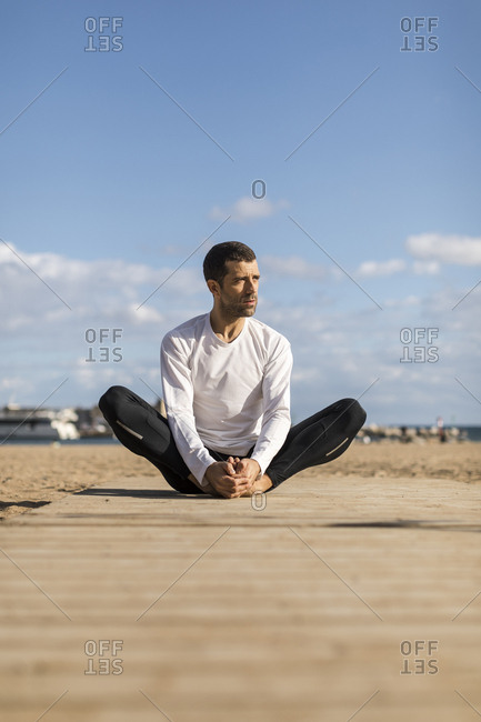 Man doing Yoga and stretching on the beach