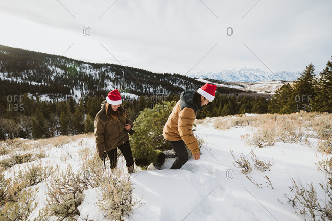 Couple drags Christmas tree up a hill in the tetons of wyoming