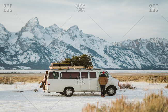 White van parked underneath the tetons with christmas tree